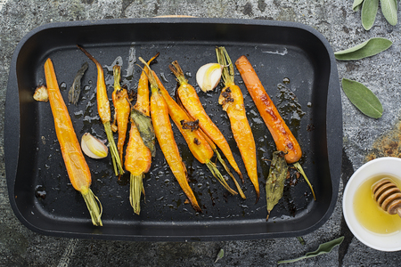 Young juicy carrots baked with honey, sage, garlic, olive oil, salt for a homely comfortable dinner on the background. Top View. Stok Fotoğraf
