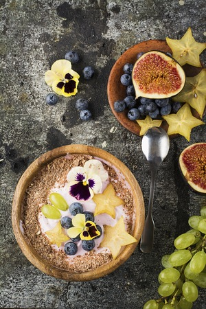A healthy breakfast snack. Smoothies bowl with berry yogurt, fresh blueberries, carambola, figs, grapes, edible flowers in a wooden bowl on a gray stone background. Top View