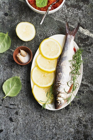 A river white fish of the Cyprinidae family on a gray stone background with herbs, lemons and salt before cooking. Top View.
