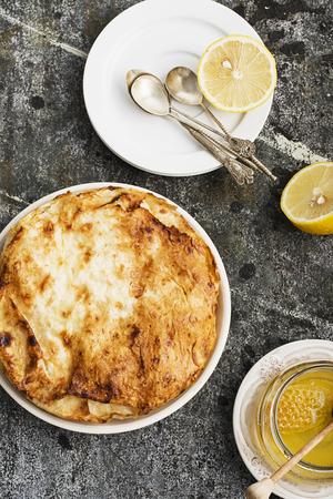 セモリナ粉のクリーム、ミルク、レモンピール、ジュース、蜂蜜とレモンと灰色の石の背景にベーキングのためのラウンド形式でギリシャのパイ。