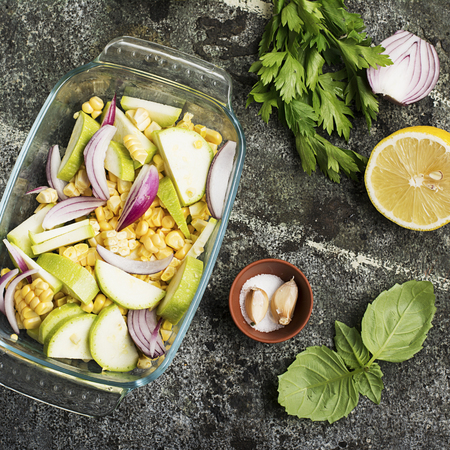 Top view of a vegetable casserole, kasserol of fresh seasonal vegetables cauliflower, corn, zucchini, red onion in a transparent form for baking for lunch..