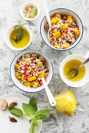 olive green: A healthy modern snack or lunch. Two bowls with pearl barley salad with slices of baked pumpkin and pomegranate seeds with butter dressing sauce. Top View.