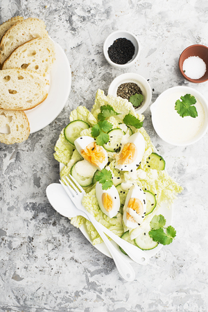 Curried egg garden salad with lettuce, fresh cucumber slices, yogurt-based curry sauce, organic eggs with black sesame and green herbs. Top View Stock Photo