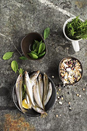 Fresh sea cold-water small fish such as smelt, sardine, anchovies on a simple background with fresh spinach, lemon slices, legumes for the concept of correct healthy natural nutrition. Top View.