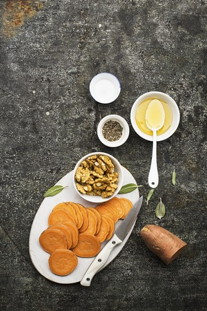 Ingredients for cooking healthy simple snacks from slices of sweet potato, walnuts with honey before baking. Top view. On a grunge gray background. Copy space