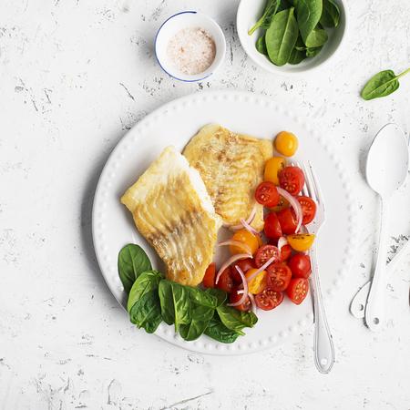 Filetto di baccalà bianco di mare fresco fritto con insalata di pomodorini e cipolle rosse dolci. concetto di cibo. vista dall'alto