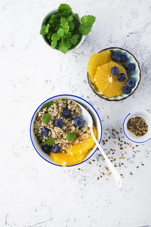 Quinoa orange blueberry bowl for breakfast with flax seeds. The concept of eating. Top View