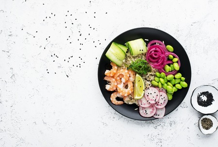 Fresh seafood recipe. Shrimp poke bowl with fresh prawn, brown rice, cucumber, pickled sweet onion, radish, soy beans edamame portioned with black and white sesame. Food concept poke bowl. Top view