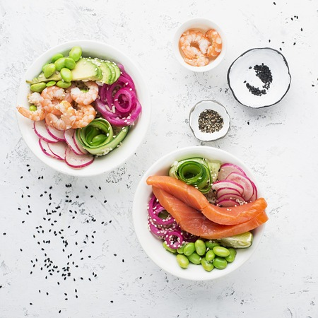 Fresh seafood recipe. Shrimp salmon poke bowl with fresh prawn, brown rice, cucumber, pickled sweet onion, radish, soy beans edamame portioned with black and white sesame. Food concept poke bowl. Top view