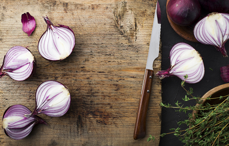 Red onions on an old vintage wooden cutting board with a knife and thyme. Top View.