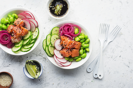 Fresh seafood recipe. Shrimp salmon poke bowl with fresh prawn, brown rice, cucumber, pickled sweet onion, radish, soy beans edamame portioned with black and white sesame. Food concept poke bowl