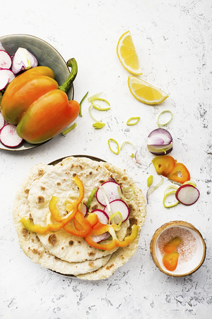 Traditional homemade flat breads for a snack with fresh seasonal vegetables, herbs and yoghurt sauce with olive oil and rose salt on the background. Top view Stock Photo