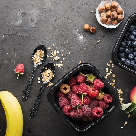 Black plastic containers take-away for a healthy snack food with raspberries, blueberries. Ingredients of healthy breakfast: granola, oat flakes, berries, nuts, apples, bananas. Top View Standard-Bild - 109075408