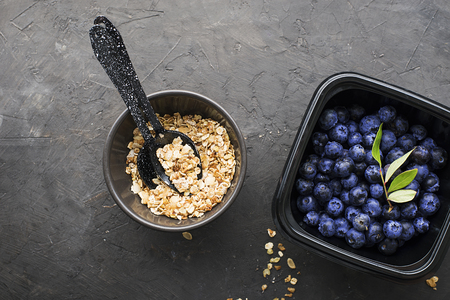 Black plastic containers take-away for a healthy snack food with raspberries, blueberries. Ingredients of healthy breakfast: granola, oat flakes, berries, nuts, apples, bananas. Top View Standard-Bild - 109075410