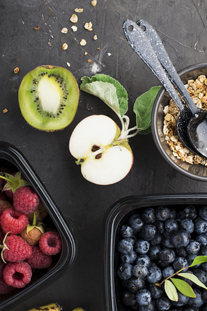 Black plastic containers take-away for a healthy snack food with raspberries, blueberries. Ingredients of healthy breakfast: granola, oat flakes, berries, nuts, apples, bananas. Top View Standard-Bild - 109075411