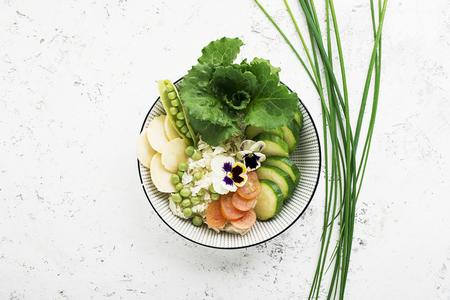 Vegetables summer fruit detox bowl. Vegetarian healthy food. Salads, lettuce leaves, raspberries, green peas, cucumber, carrots, daikon, edible flowers Top View. Standard-Bild - 109075412