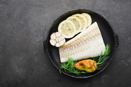 A dish of healthy cuisine with seafood: cod is a white sea fish with lemon slices, olives, sea salt in a cast-iron black frying pan. Top view Standard-Bild - 109064709
