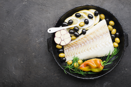 A dish of healthy cuisine with seafood: cod is a white sea fish with lemon slices, olives, sea salt in a cast-iron black frying pan. Top view Standard-Bild - 109064708