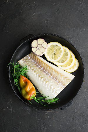 A dish of healthy cuisine with seafood: cod is a white sea fish with lemon slices, olives, sea salt in a cast-iron black frying pan. Top view Standard-Bild - 109064711