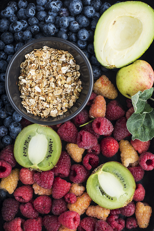 Healthy food: a lot of ingredients of proper food, blueberries, kiwi, raspberries, granola, oatmeal, honey, organic health products. Top view.