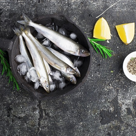 Fresh sea fish smelt or sardines ready for cooking with lemon, thyme, rosemary and coarse sea salt. The concept of fresh, healthy seafood. Top view