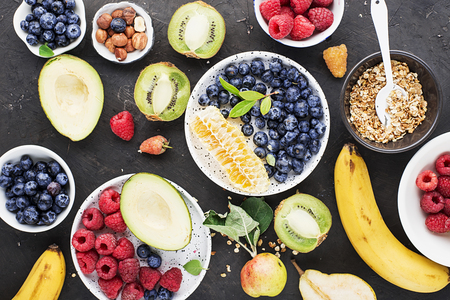 Ingredients of a healthy breakfast: raspberries, blueberries, oat flakes, granola, honey, nuts, banana, avocado kiwi on the background Top View