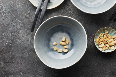 Gray serving plates on a dark gray background for serving lunch. A few peanuts nuts in the frame. Top view.