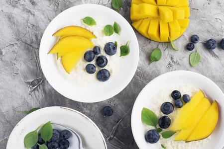 Milk porridge for breakfast with slices of mango and fresh blueberries. Top view. Standard-Bild - 115334407