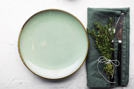 Table gentle simple serving in shades of green with a bunch of thyme on a light background. Top view.