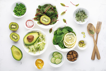 Green ingredients for spring detox salads: spinach, sorrel with red veins, cucumbers, radishes, iceberg lettuce, green peas, avocados, lemon, microgreen, yellow tomatoes on a white background with wooden cutlery. Top view.