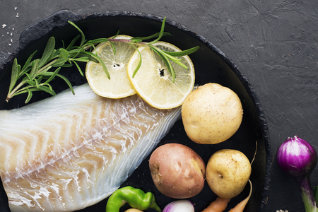 Cod. Fresh sea white raw fish before cooking in a with fresh vegetables: sweet onions, and lemons. Top view. Food concept