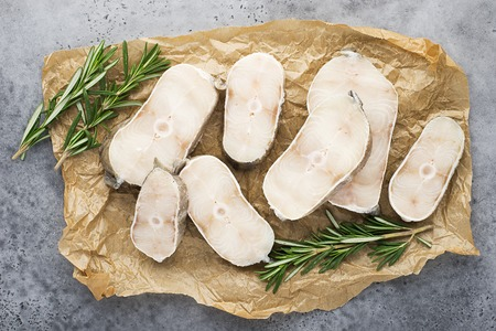 Sea white fish cod steaks raw on paper with sprigs of rosemary and lemon slices on a light gray background. Top view