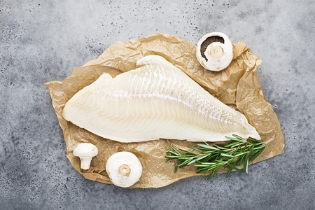 Filetto di baccalà bianco su pergamena con funghi prataioli crudi freschi prima della cottura. Cucina a zero sprechi. Cibo sano a base di pesce. Vista dall'alto, spazio