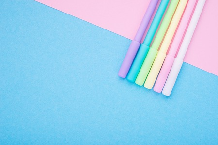 Universal bright background with multicolored pens, felt-tip pens, markers, trendy stationery on a delicate pink and blue, two tones of a two-color substrate. Top view. Horizontal. Place for text