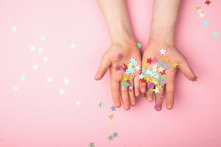 Gold glitter stars on childrens hands.
