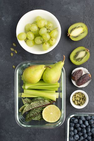 Healthy food fresh ingredients vegetables fruit berries seeds. Glass containers for lunch with juicy celery, lime, lettuce, sorrel, kiwi, grapes, blueberries, pears, pumpkin seeds, dried fruits on a dark background. Balanced and vegetarian clean diet. Top view Stok Fotoğraf