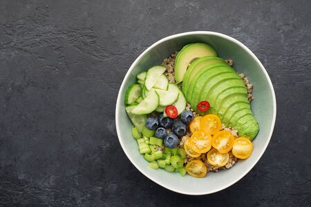 Healthy vegetable wholegrain bowl. Quinoa, avocado, cherry tomatoes, juicy celery, blueberries, hot peppers balanced lunch breakfast. Without meat. Top view. On a dark background