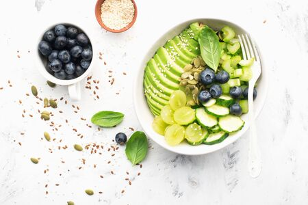 Green vegetables fruit detox balance salad bowl. Avocados, cucumbers, cherry tomatoes, blueberries, celery, grapes. Juicy cream crispy dish without meat. Top view