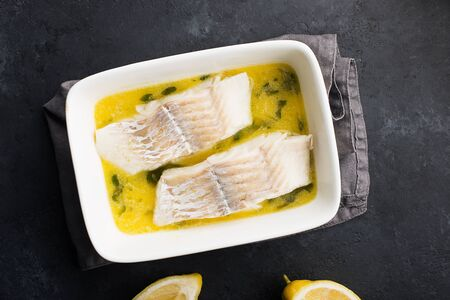 Steamed cod fillet butter-lemon sauce with herbs in the oven. Top view. In a baking dish. Healthy eating Stockfoto