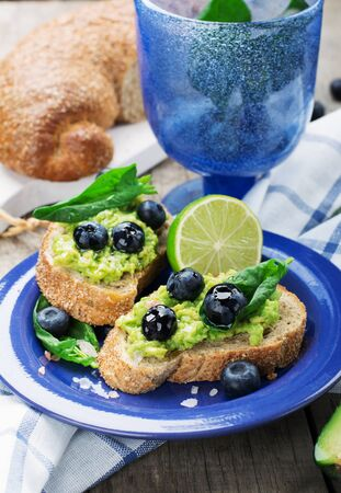 Toasts with mashed avocado and blueberries, spinach and butter on a wooden