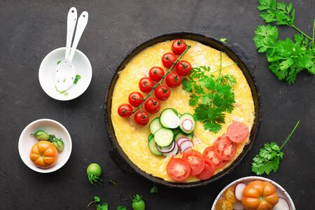 One pan dish. Homemade farm egg omelet with fresh, seasonal, natural vegetables and herbs. Tomatoes, cucumbers, radishes, parsley, organic egg. Healthy, simple nutrition. Top view