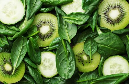 Green juicy fruits vegetables background. Kiwi, spinach, cucumbers, juicy salad leaves, spinach as a healthy diet, clean cosmetics, green life. Top view. Copy space,