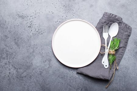Table set white plate, white spoon and white enamelled fork on a gray modern background. With a linen gray napkin. Monochrome true trend. Minimalism style. Top view,