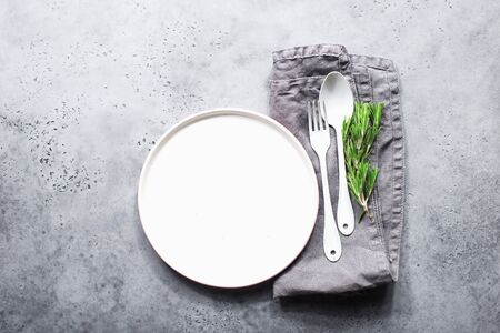 Table set white plate, white spoon and white enamelled fork on a gray modern