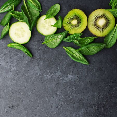 Green juicy fruits vegetables background. Kiwi, spinach, cucumbers, juicy salad leaves, spinach as a healthy diet, clean cosmetics, green life. Top view. Copy space