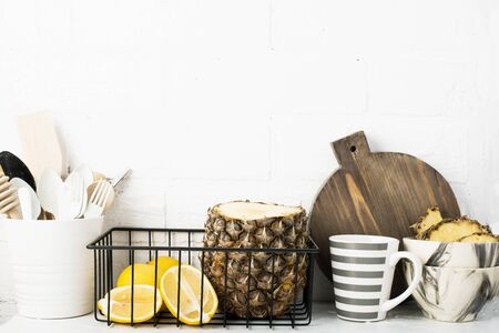 Kitchen shelf lifestyle white background with fresh lemons, pineapple, kitchen tools, appliances, chopping boards, storage baskets. Eco-friendly life. Home style, minimalism, healthy eating.