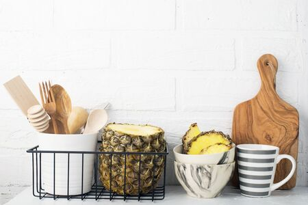 Kitchen shelf lifestyle white background with fresh lemons, pineapple, kitchen tools, appliances, chopping boards, storage baskets. Eco-friendly life. Home style, minimalism, healthy eating