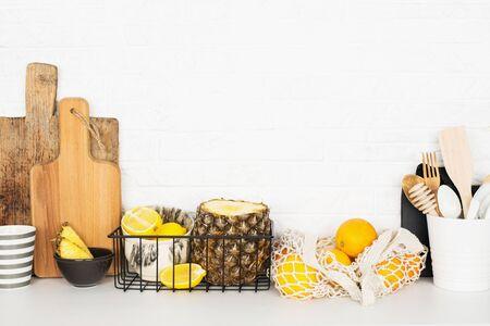 Kitchen shelf storage organization fruit cutlery. Home style minimalism zero waste. Still life with storage baskets of pineapple, oranges, lemons on a white brick background. The modern trend of scandi is simplicity, comfort., 版權商用圖片