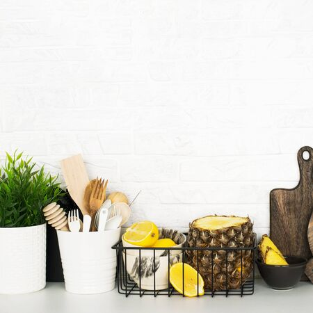Kitchen shelf with baskets for storing products, pineapple, lemons, cutlery in a glass, chopping wooden boards on a white brick background. Style home scandi minimalism trend of modernity. Copy space,
