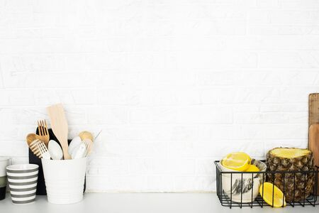 Kitchen shelf with baskets for storing products, pineapple, lemons, cutlery in a glass, chopping wooden boards on a white brick background. Style home scandi minimalism trend of modernity. Copy space 版權商用圖片